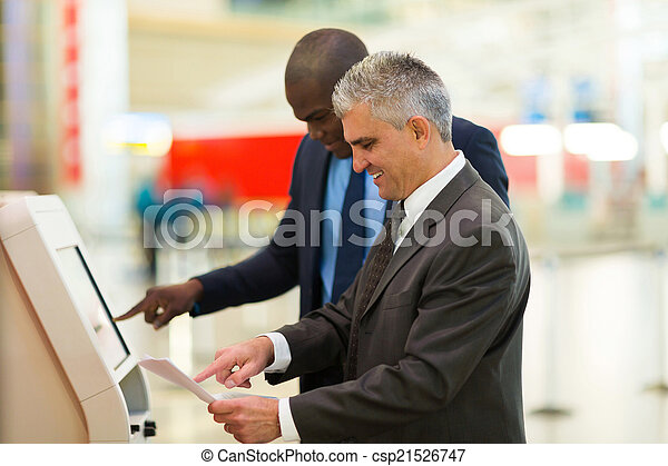 business travellers using self help check in machine at airport - csp21526747
