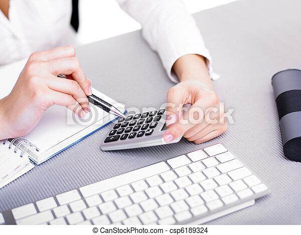 Business woman calculating with calculator - csp6189324