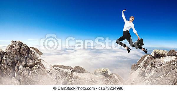 Business woman jumps through the gap between hills. - csp73234996