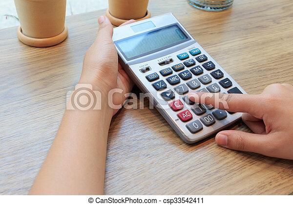 Business woman pressing calculator buttons - csp33542411