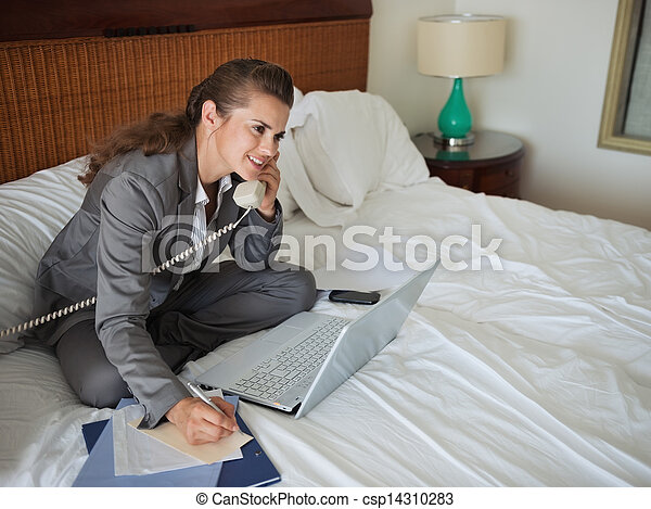 Business woman sitting on bed in hotel room and talking phone - csp14310283