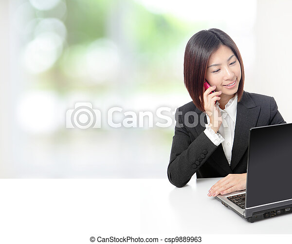 business woman speaking phone and using computer - csp9889963