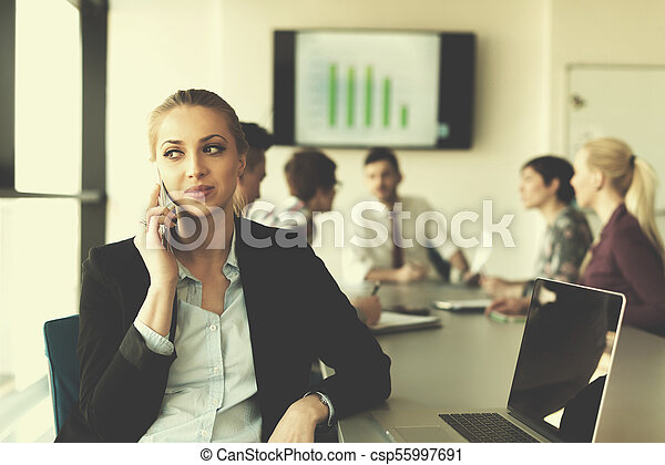 business woman speeking on phone at office with team on meeting in background - csp55997691