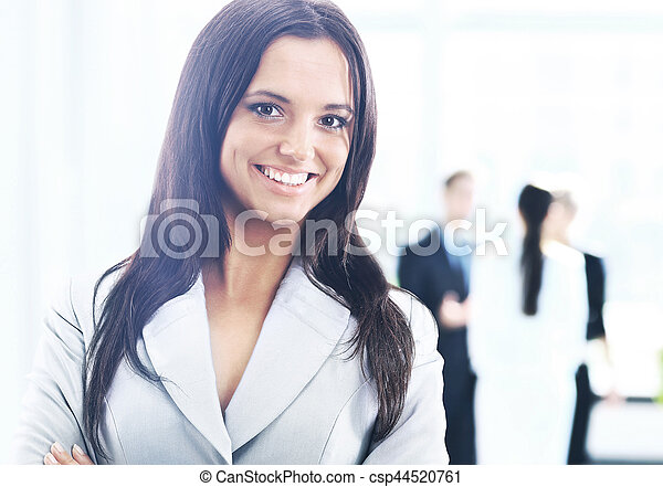 business woman standing with her staff in background at office - csp44520761