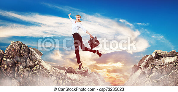 Business woman stands unstable on mountain cliff. - csp73235023