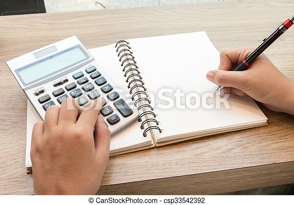 Business woman using calculator for calculating data - csp33542392