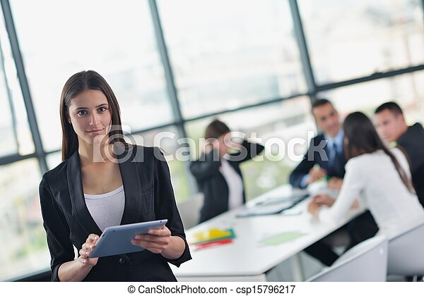 business woman with her staff in background at office - csp15796217