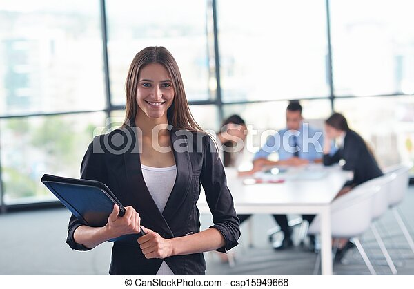 business woman with her staff in background at office - csp15949668