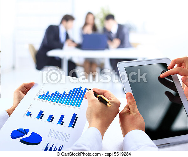 Business work-group analyzing financial data in office - csp15519284