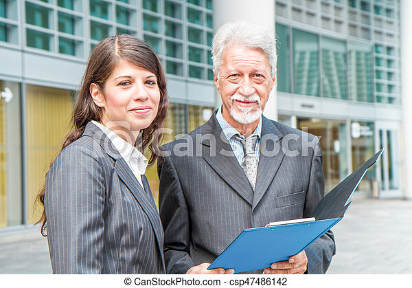 Businessman And Businesswoman discussing a project - csp47486142