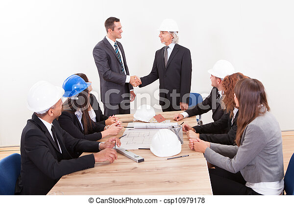 Businessman And Engineer Shaking Hands - csp10979178