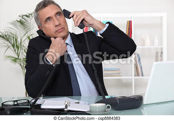 Businessman answering ringing telephones - csp8884383