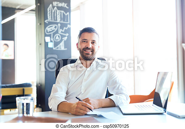 Businessman at the desk with laptop in his office. - csp50970125
