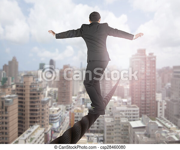 Businessman balancing on a wire with sky clouds cityscape - csp28460080