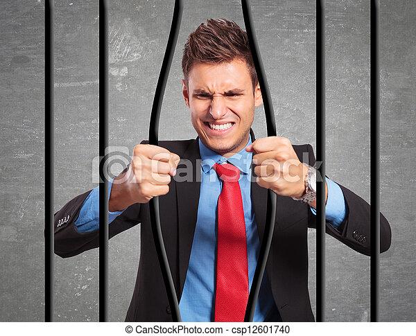 businessman bending the bars of his prison - csp12601740
