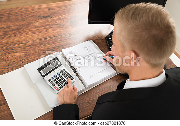 Businessman Calculating Invoice At Desk In Office - csp27821870