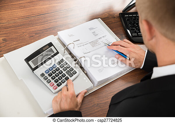 Businessman Calculating Invoice At Desk In Office - csp27724825