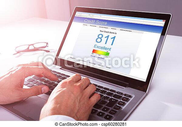 Businessman Checking Credit Score On Laptop - csp60280281