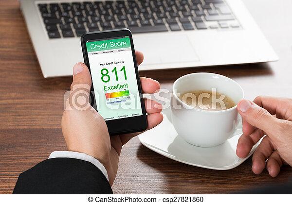 Businessman Checking Credit Score On Cellphone - csp27821860