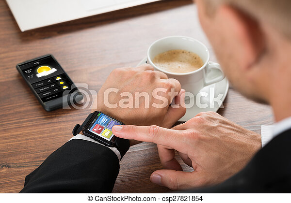 Businessman Checking Weather On Smartwatch - csp27821854