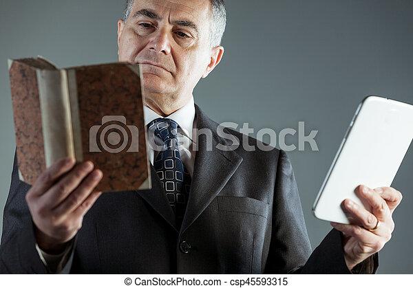 Businessman deciding between a book or e-book - csp45593315