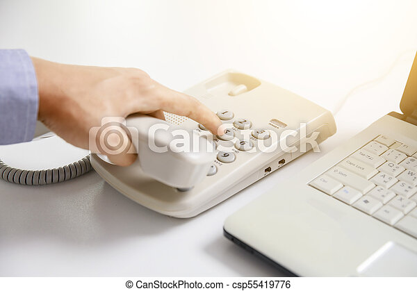 businessman dial digital telephone with office background - csp55419776