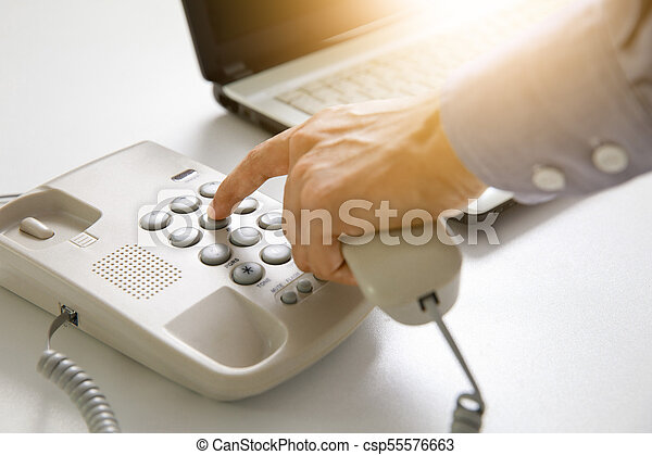 businessman dial digital telephone with office background - csp55576663