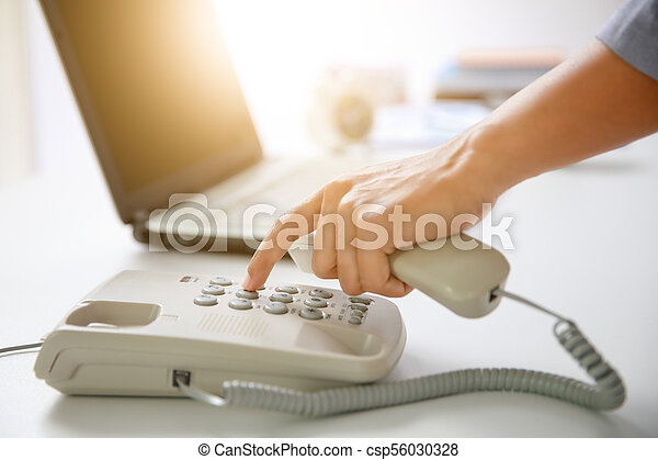 businessman dial digital telephone with office background - csp56030328