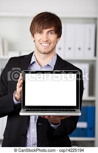 Businessman Displaying Laptop In Office - csp14225194