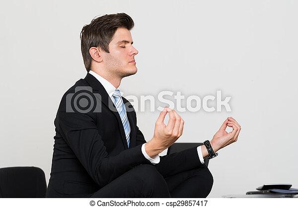 office meditation. Businessman Doing Meditation In Office - Csp29857417