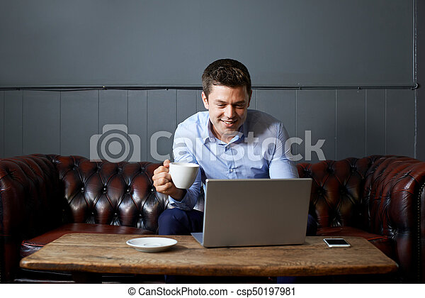 Businessman Drinking Coffee Whilst Working On Laptop In Internet Cafe - csp50197981