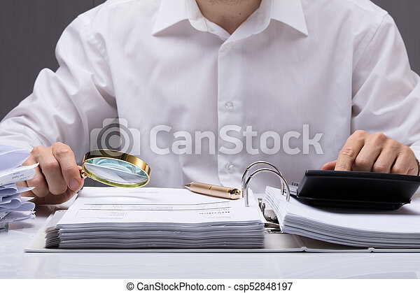 Businessman Examining Invoice With Magnifying Glass - csp52848197