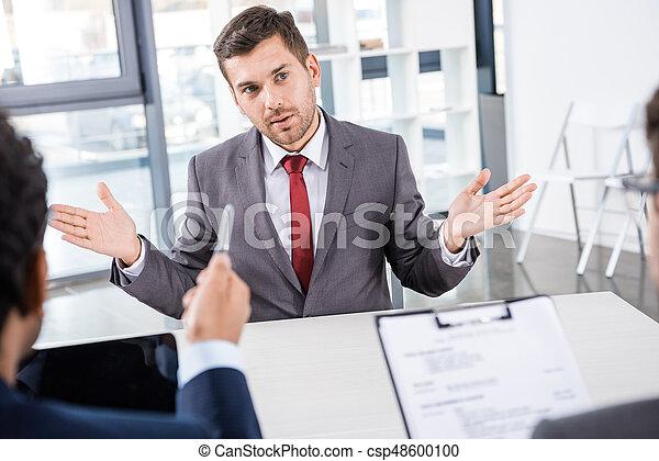 businessman gesturing during job interview, business concept - csp48600100