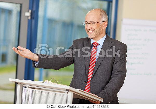 Businessman Gesturing While Standing At Podium - csp14213513