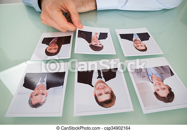 Businessman Hand Choosing Photograph Of A Candidate - csp34902164