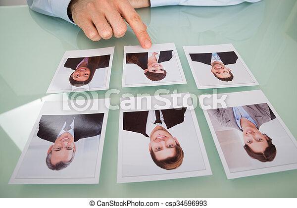 Businessman Hand Choosing Photograph Of A Candidate - csp34596993