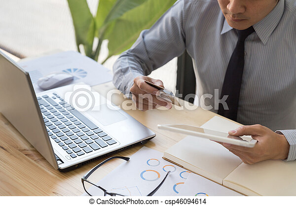 Businessman hand holding a Credit card intent to made a online payment with digital tablet on his desk. - csp46094614