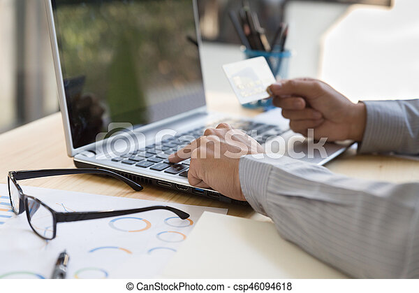 Businessman hand holding a Credit card intent to made a online payment with his computer laptop on his desk. - csp46094618