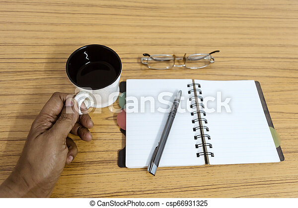 Businessman holding a cup of coffee. Business pocket planner with a eyeglass and a pen ready to note an appointment. Business still life concept with office stuff on table. Blank pages ready for text. - csp66931325