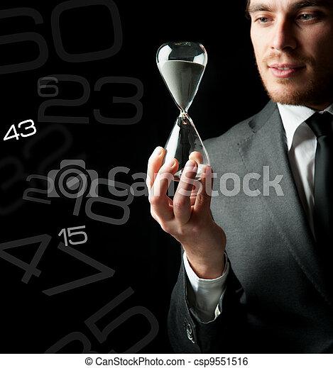 Businessman holding a hourglass - csp9551516