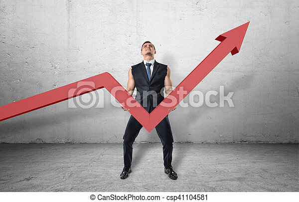 Businessman holding big red line graph with an upturned arrow and trying to raise it up - csp41104581