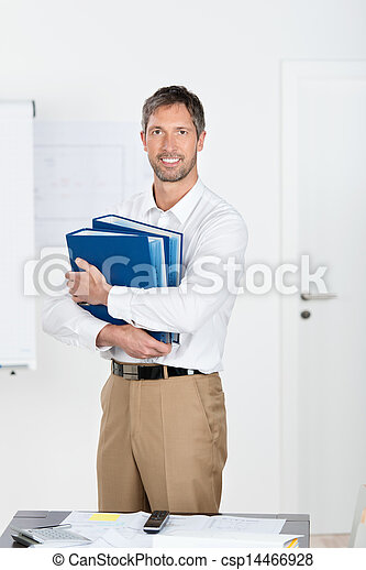 Businessman Holding Binders In Office - csp14466928