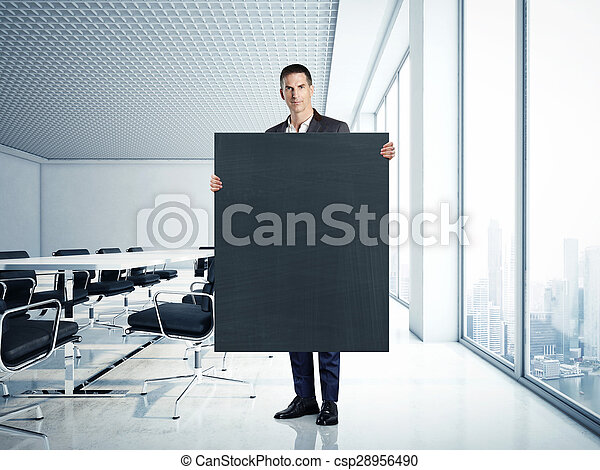 Businessman holding blank blackboard at contemporary office - csp28956490