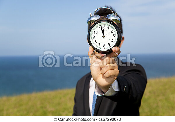 businessman holding clock and standing on the field - csp7290078