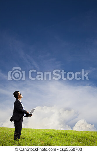 Businessman holding computer and watching the cloud - csp5558708