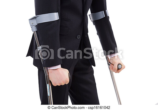 Businessman in a suit holding crutches - csp16161042