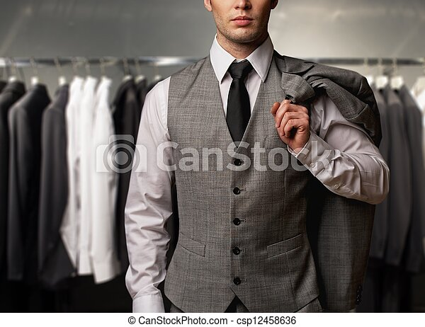 Businessman in classic vest against row of suits in shop - csp12458636