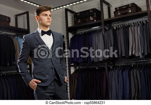 Businessman in classic vest against row of suits in shop. A young stylish man in a jacket. It is in the showroom, trying on clothes, posing. Advertising photo - csp55864231
