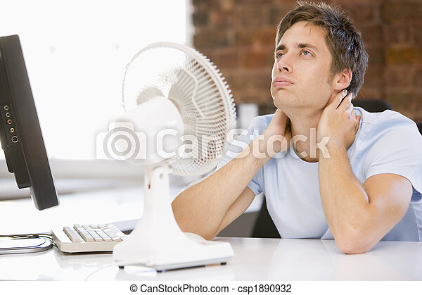 Businessman in office with computer and fan cooling off - csp1890932