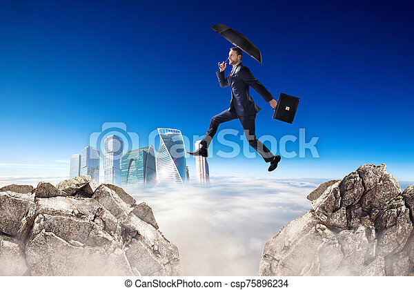 Businessman jumping over a cliff with umbrella over blue sky background. - csp75896234